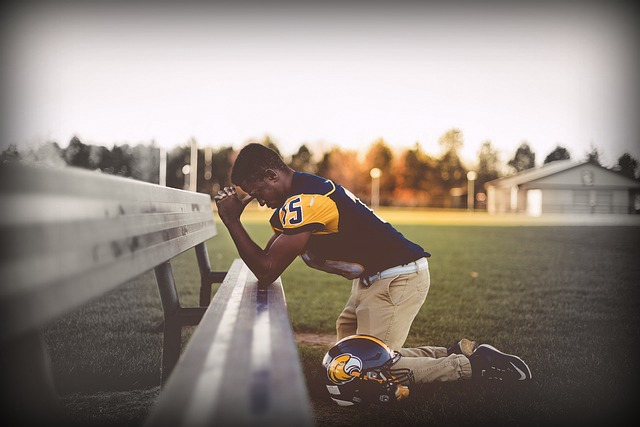 Football player kneeling in prayer