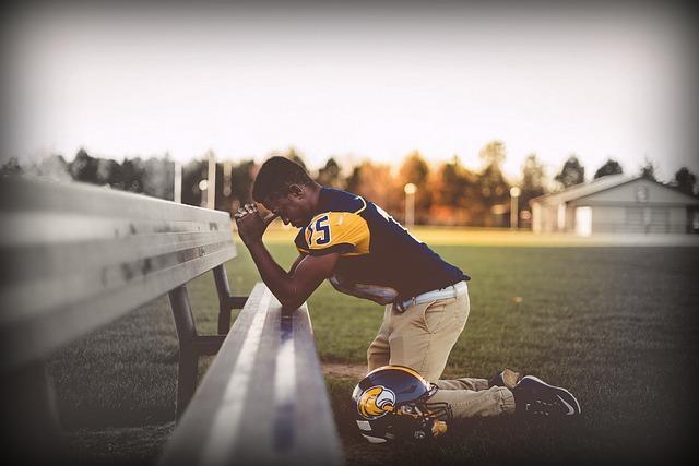 Football player kneeling in prayer