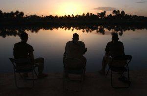 Three men sitting, facing a lake.