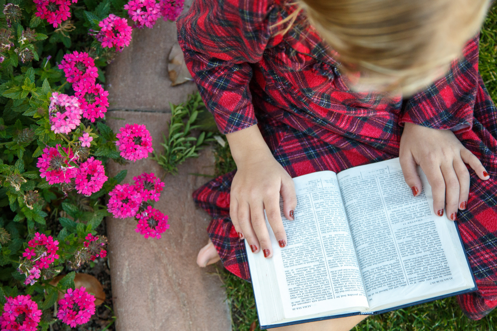 A young girl sits in a garden and reads the Book of Mormon. via lds.org © intellectual reserve